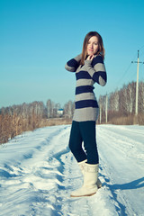 Young brunette girl in the snow field. Winter