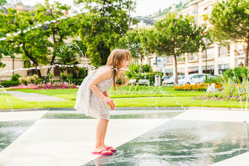 Cute little girl playing with a fountain on a nice summer day