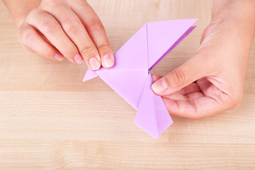 Female hands holding origami bird on wooden table, close up
