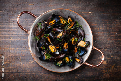 Fotobehang Schaaldieren Boiled mussels in copper cooking dish on dark wooden background