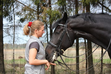 Young blonde woman and black horse smiling