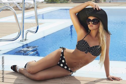 beautiful blond woman in sunglasses near pool.sexy woman in hat