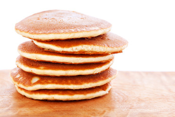 Stack of pancakes on wooden board with white background