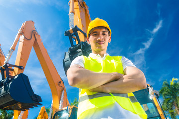 Asian construction worker in front of shovel excavator