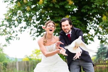 Brautpaar mit fliegenden weißen Tauben