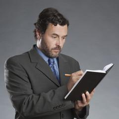 Geschäftsmann schreibt in Kalender