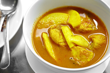 close up thai spicy yellow fish curry in white bowl