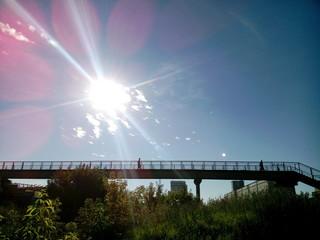 Мост на фоне неба и солнца.