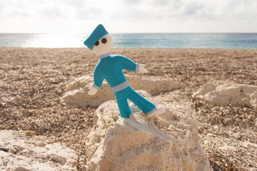 Blue stuffed doll on the beach