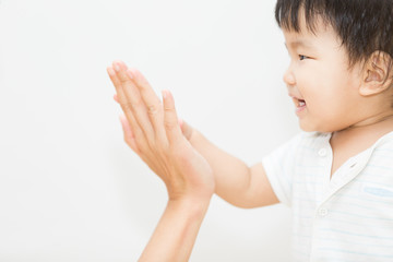 isolate cute asian baby touch hand with mother