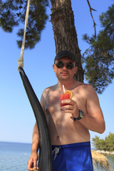 Man drinking cocktail on the beach