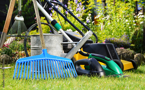 Watering can and tools in the garden - 67835981