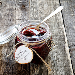 "Cherry jam in a jar with the word ""homemade"""