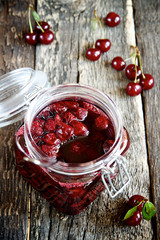 Cherry jam in a glass jar on a shabby old wooden background
