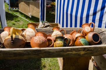clay jugs lying in wooden trough at village market