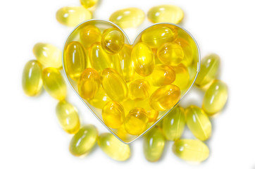 fish oil pills on heart shape box on white background isolated