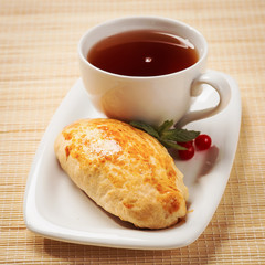 Freshly baked pie with jam and cup of black tea