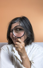 Funny image of a adult woman with a magnifying glass, one eye is