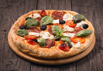 Pizza with salami, mozzarella, olives and basil on rustic wooden