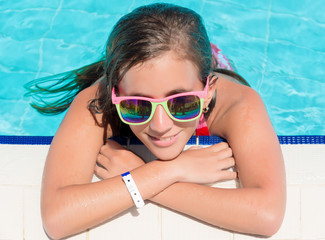 Girl smiling at the edge of a swimming pool