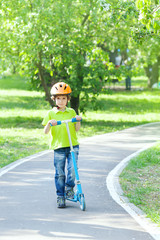 Boy dressed in a safety helmet stands with kick scooter