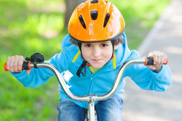 The small boy in blue fleece jacket ride a cycle
