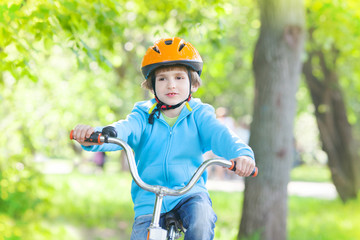 Young child riding bicycle or bike in summer park