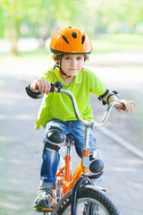 The boy rides a cycle on a bicycle trail in city park