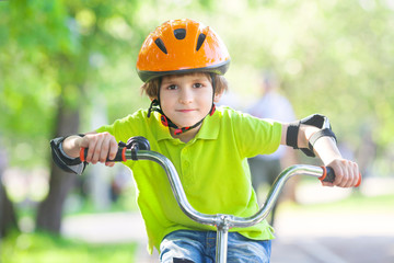 boy in a safety helmet rides a Bicycle on a Bicycle tracks