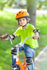 Child rides bike outdoors dressed in helmet