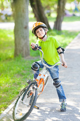 Young boy trying to ride bicycle in city park