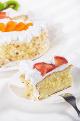 Slice of fresh fruit flan cake with cream
