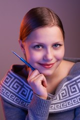 Teen girl smiling with pen in her hand, portrait