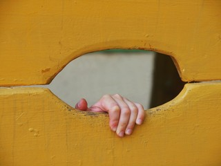 Children hand with small fingers through hole in yellow wooden