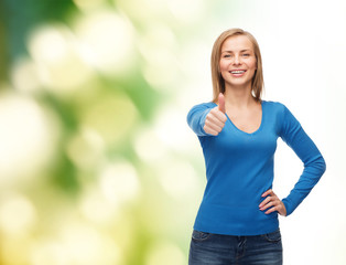 smiling girl in casual clothes showing thumbs up