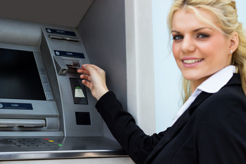 Smiling businesswoman at the ATM