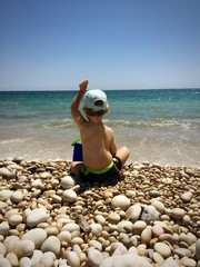 back of a child playing with stones on the beach