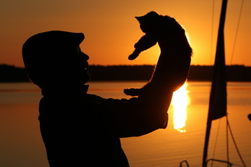 człowiek i kot o zachodzie słońca