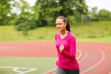 smiling young woman running on track outdoors