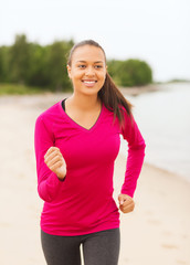smiling woman running on track outdoors