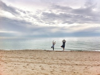 two people practicing yoga on the beach