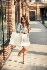 happy woman with white paper bag at shopping mall