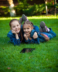 two girls having fun on grass with tablet