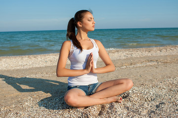young woman practicing yoga or fitness at seashore