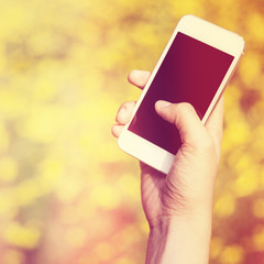 Woman hand holding smartphone against spring green and yellow fl