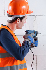 Builder drilling brick wall