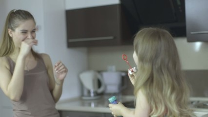 Young mother and daughter blowing bubbles in the kitchen.