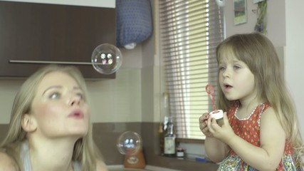 Happy mother and daughter blowing bubbles in the kitchen.