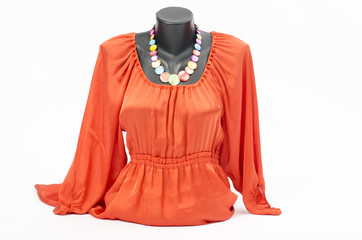 Orange blouse on mannequin with matching accessories
