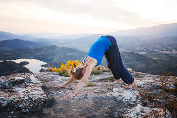 Young Caucasian woman performing downward dog yoga pose